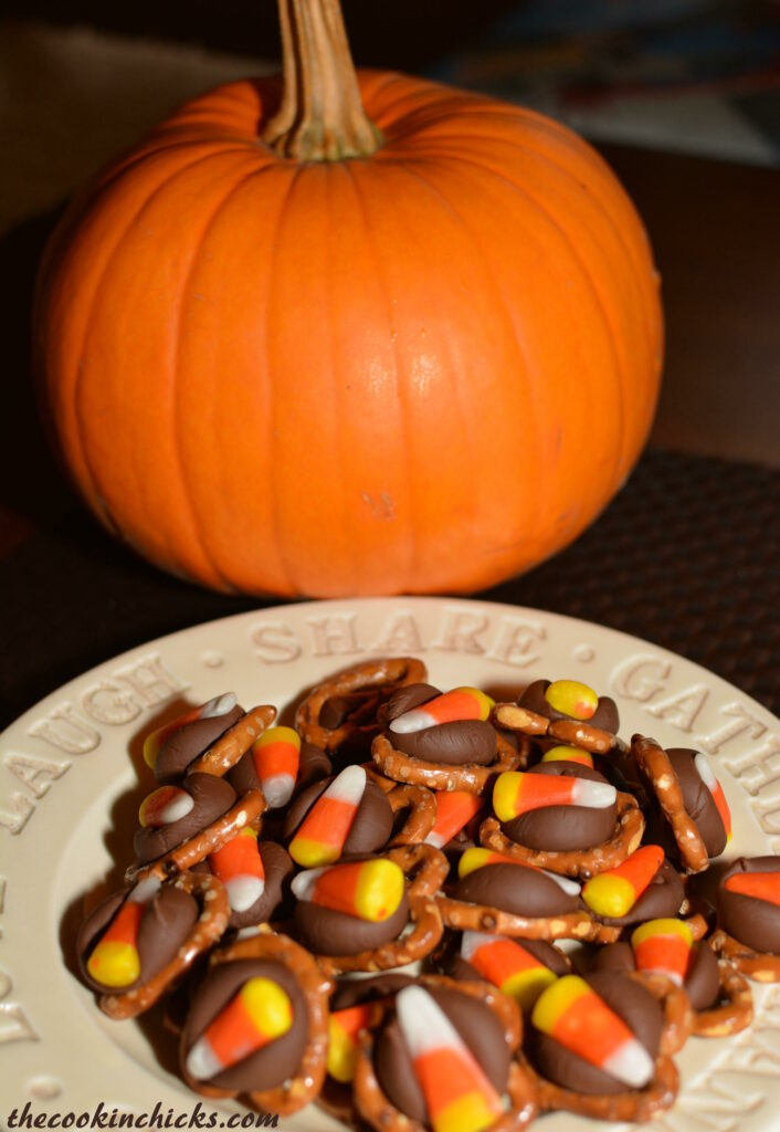 bite sized halloween treats made with pretzels, hershey kisses, and candy corn