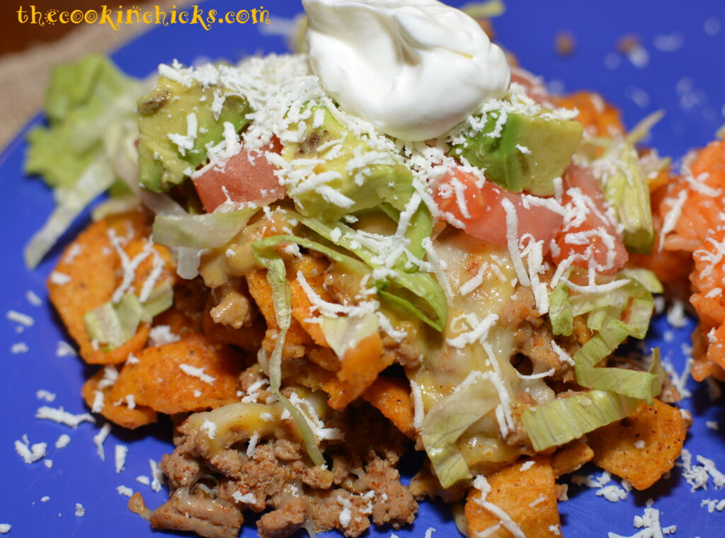 layers of fritos, beef, cheese, and toppings to make a tex mex meal