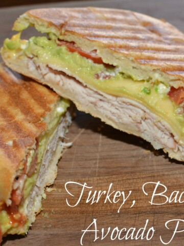 layers of turkey, avocado, and bacon combined into a panini