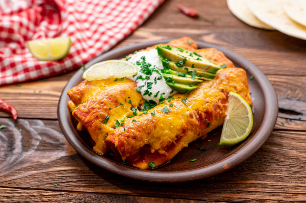 Plated easy beef enchiladas with sour cream