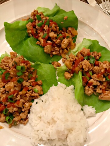 cooked, asian flavored chicken wrapped in a lettuce leaf as an appetizer or main meal