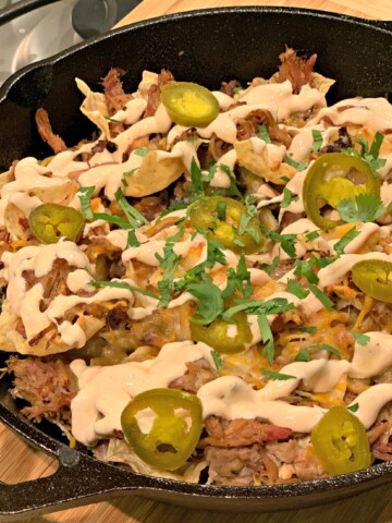 flavor packed loaded nachos with toppings, meat, and a sour cream sauce