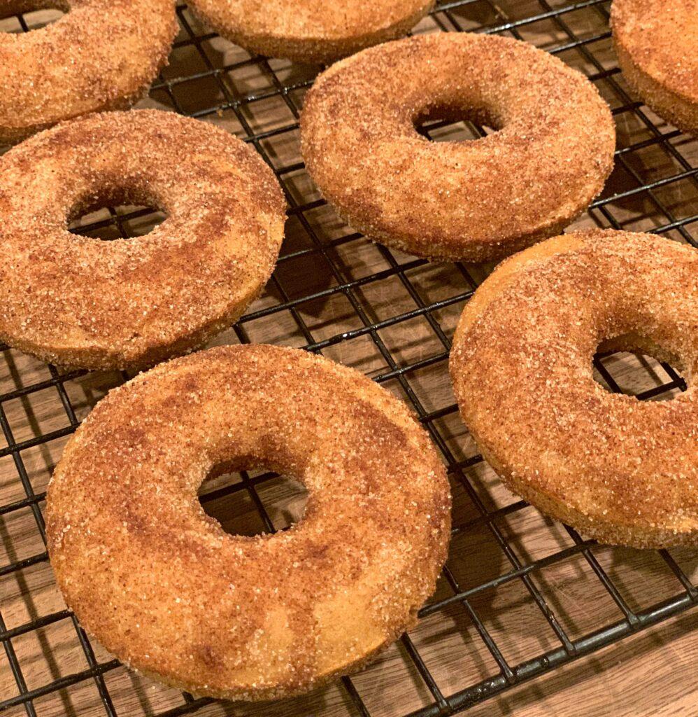 cinnamon and sugar sprinkled over a baked apple cider donut