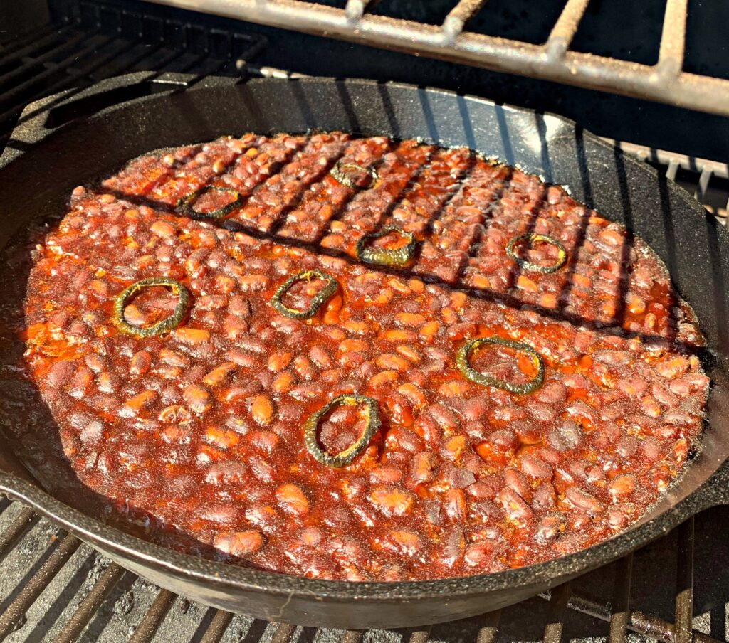 Beans in a cast iron skillet on the smoker