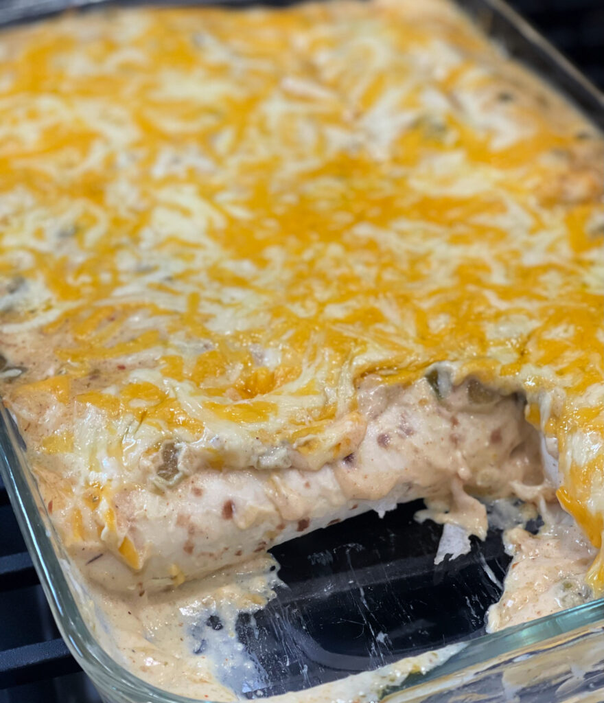 Melted cheese over a white cream sauce that coats shredded chicken enchiladas.