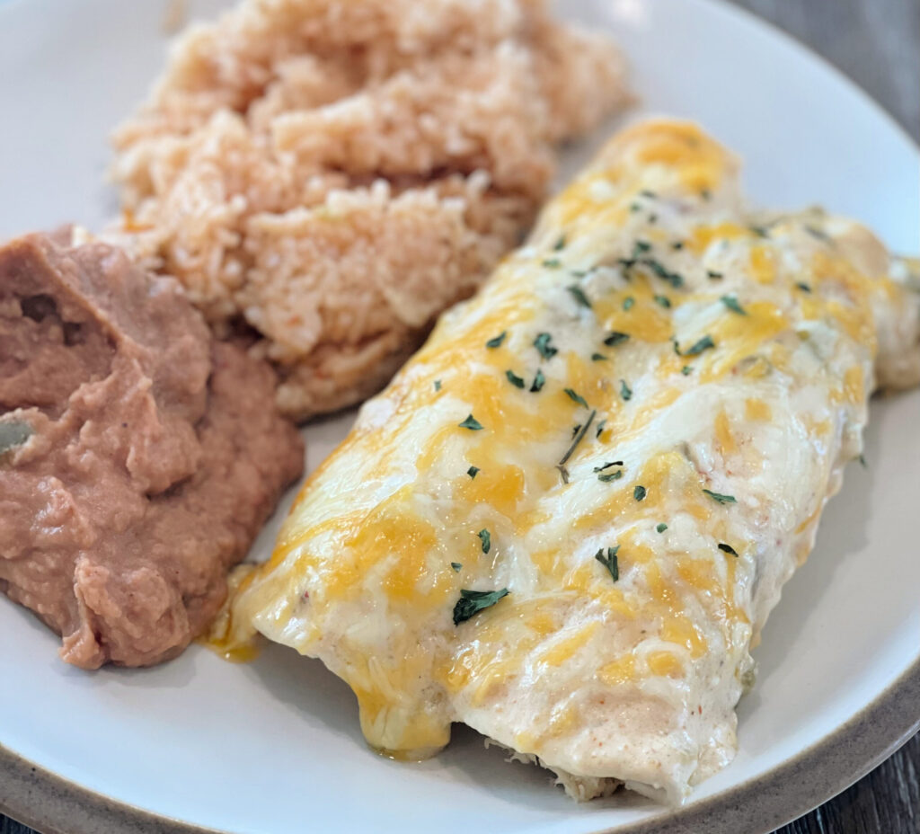 Creamy chicken enchiladas served on a plate with rice and beans.