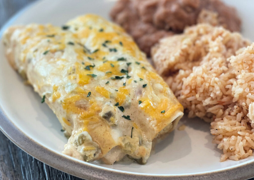 Creamy white chicken enchiladas served with refried beans and Mexican rice.