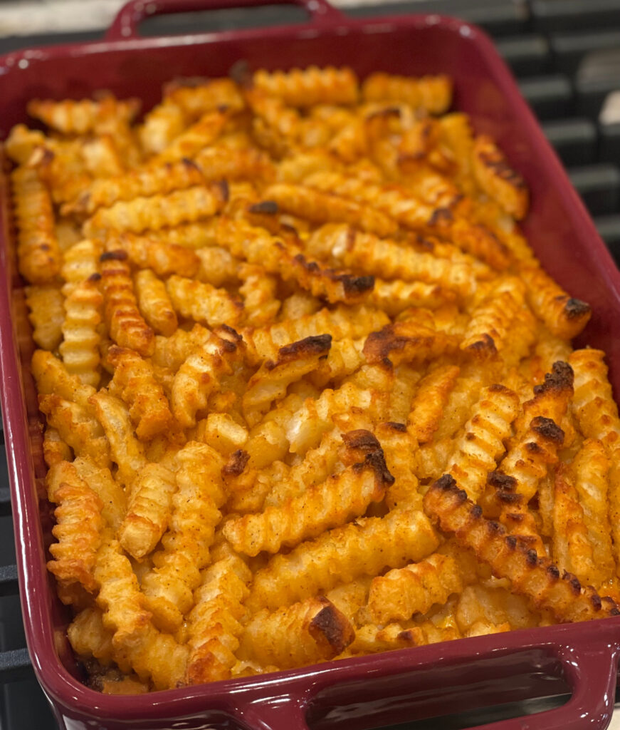 french fries and a ground beef mixture layered into a cheesy casserole