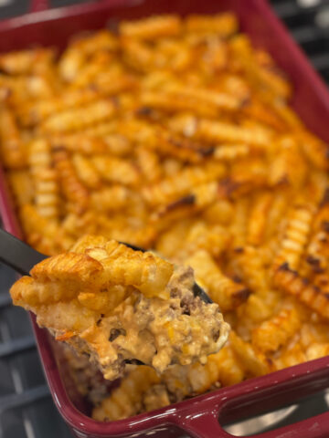 seasoned french fries on top of a cheesy, ground beef mixture